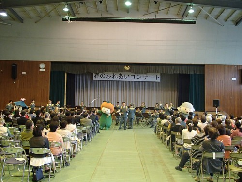 五條のゆるキャラ「ゴーチャン」「カッキー」 「星博士」と「Go !Go!五條のゴーカスター」の演 奏の中、歌唱する音楽隊員
